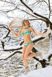 Blonde woman jumping on the snow Royalty Free Stock Photos