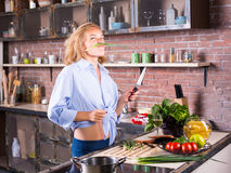 Blonde woman on kitchen playing with green onion stock photos
