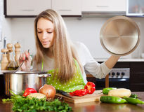 Blonde woman with ladle testing soup from pan Royalty Free Stock Image