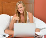 Blonde woman with laptop - bedroom Stock Image