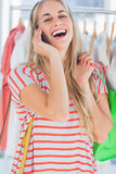 Blonde woman laughing in a clothing store Stock Images