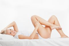 Blonde woman laying on bed. Beautiful blonde woman laying on white bed and touching her leg Royalty Free Stock Photography