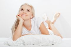 Blonde woman laying on bed. Beautiful blonde woman laying on white bed with pillow and looking up Stock Photo