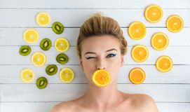 Blonde woman laying next to slices of orange, lemon and kiwi Stock Images