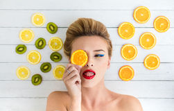 Blonde woman laying next to slices of orange, lemon and kiwi Stock Image