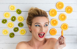 Blonde woman laying next to slices of orange, lemon and kiwi Royalty Free Stock Image