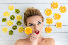 Blonde woman laying next to slices of orange, lemon and kiwi Royalty Free Stock Images