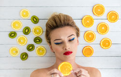 Blonde woman laying next to slices of orange, lemon and kiwi Stock Photography