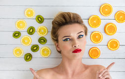 Blonde woman laying next to slices of orange, lemon and kiwi Royalty Free Stock Photo