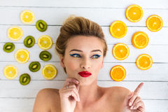 Blonde woman laying next to slices of orange, lemon and kiwi Stock Photos