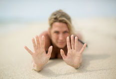 Blonde woman lays on beach sand, sandy hands Royalty Free Stock Photography