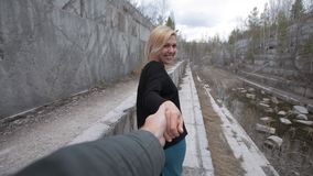 Blonde woman leads the guy by the hand behind him stock footage