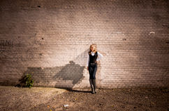 Blonde woman leaning against long tiled wall on street Royalty Free Stock Photos