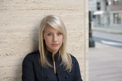 Blonde Woman Leaning Against Wall Stock Image