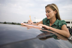 Blonde woman leaning on stationary car roof, writing on piece of paper in folder, smiling Royalty Free Stock Photography
