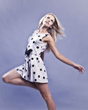 Blonde woman leaping in white dress Stock Image