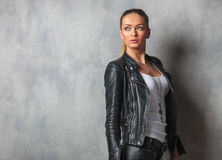 Blonde woman in leather jacket looks up to side Stock Images
