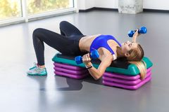 Blonde woman lie on step platform and doing butterflie exercise. Studio shot Stock Images
