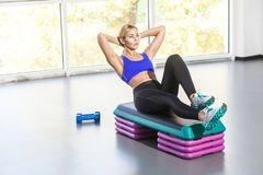 Blonde woman lie on step platform and doing press aerobic. Studio shot Royalty Free Stock Image