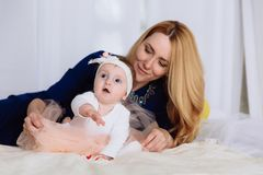 The blonde woman lies on the bed and straightens her skirt to her little daughter. The baby pulls the handles up and stock photography