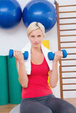 Blonde woman lifting dumbbells on exercise ball Royalty Free Stock Photos