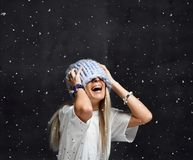 Blonde woman in light blue knitted hat happy smiling sitting under snowflakes winter time royalty free stock image