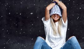 Blonde woman in light blue knitted hat happy smiling sitting under snowflakes winter time stock photo