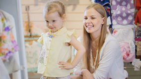 Blonde woman with little daughter buying kids dress in clothes store Stock Images
