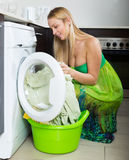 Blonde woman loading clothes into washing machine Royalty Free Stock Images