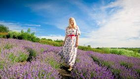 Happy blonde woman in long dress standing on lavender field stock photography