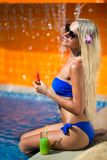 Blonde woman long hair eat watermelon near pool. Young slim blonde woman with long hair in sunglasses eat watermelon and drinks guava juice suntan near the royalty free stock image