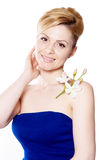 The blonde woman with long hair holding a flower orchid isolated. On the white background Royalty Free Stock Photos