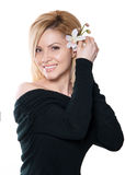 The blonde woman with long hair holding a flower orchid isolated. On the white background Stock Photo