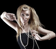 Blonde woman with long hair and a pearl beads on dark background. Royalty Free Stock Images