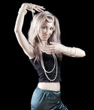 Blonde woman with long hair and pearl dances an oriental dance on dark background. Royalty Free Stock Images