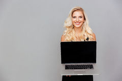 Blonde woman with long hair showing blank laptop computer screen Stock Photos