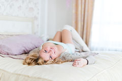 Blonde woman with long hair smiling and lying on whit Royalty Free Stock Images