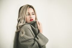 Fashion blonde woman standing against wall stock images