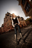 Blonde woman with long legs standing on street against old building Royalty Free Stock Photography