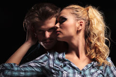 Blonde woman looking away and embracing her boyfriend Stock Photo