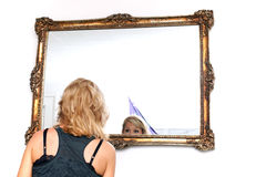 Blonde woman looking in mirror. Pretty blonde woman seen from behind is looking at herself in large ornate mirror with only her eyes visible Royalty Free Stock Photos