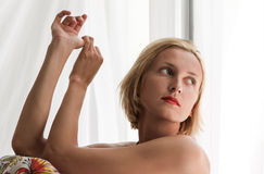 Blonde woman looking out the window. With her elbows on her knees her fingers of one hand holding the thumb of the other Stock Photo