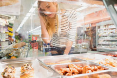 Blonde woman looking at prepared meal buffet Royalty Free Stock Photography