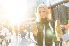 Blonde woman looking at smart phone in London Royalty Free Stock Photo