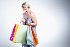 Blonde woman looking to her shopping bags Royalty Free Stock Photography