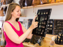 Blonde woman looking to jewelry stand and chooses errings in sto Royalty Free Stock Image