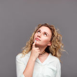 Blonde woman looking up touching chin Stock Photos