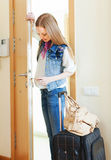 Blonde woman with luggage loocking door lock. And leaving her home Royalty Free Stock Images
