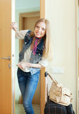 Blonde  woman with luggage loocking door Royalty Free Stock Images