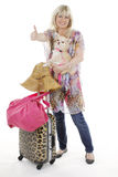 Blonde woman with luggage and small dog. Blonde woman smiling with small chihuahua dog waiting with her luggage holds her thumb up Royalty Free Stock Image